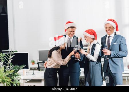 Heureux les jeunes collègues de santa hats boire du vin et de célébrer Noël au lieu de travail Banque D'Images