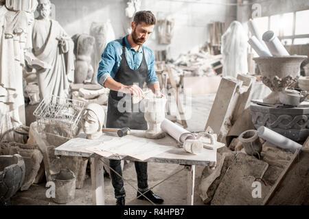 Dans l'homme Tee-shirt bleu et un tablier travaillant dans l'ancien studio atmosphérique vase en pierre de brossage sur la table