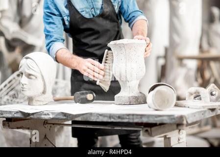 L'homme travaillant avec vase en pierre sur le lieu de travail dans l'ancien studio. Vue rapprochée avec pas de visage