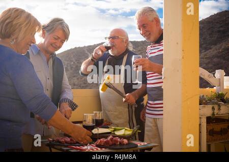 Les gens dans l'amitié les couples d'âge mûr ont ensemble un barbecue à la maison l'alimentation et de profiter de la vie à la retraite et le jour - une célébration d'amis Banque D'Images