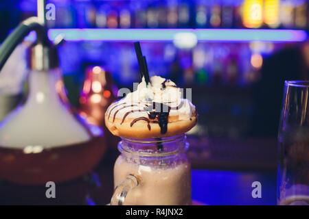 Milkshake avec donuts. Cocktail bleu lait sissy se dresse sur la table dans le café sur fond sombre. Banque D'Images