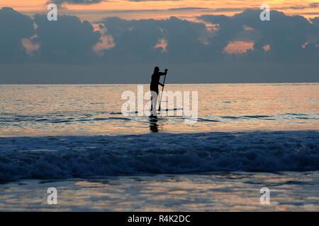 Stand Up Paddle boarder sur mer calme au coucher du soleil d'or