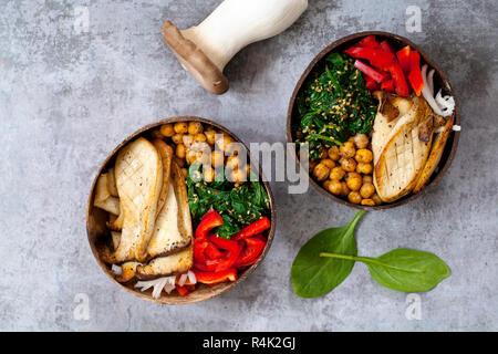 Bol Bouddha vegan avec king pleurote, pois chiches, épinards et au poivron rouge Banque D'Images