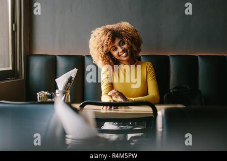 Smiling afro american woman sitting at a table de restaurant en attente de quelqu'un. Cheerful businesswoman sitting in a restaurant avec son sac par son sid Banque D'Images