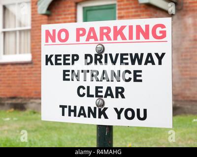 Un signe extérieur d'une chambre pour dire no parking garder entrée effacer merci le rouge et le blanc et noir sur l'après clouée vissée Banque D'Images