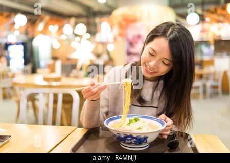 Femme jouira de ses nouilles dans un restaurant japonais Banque D'Images