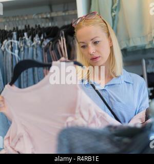 Belle femme shopping des vêtements à la mode dans une boutique de vêtements. Banque D'Images