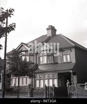 1940, historiques, une dame debout à l'entrée d'un semi-détaché à deux étages maison de banlieue, England, UK. Construite dans les années 1920, la chambre avait des fenêtres à battants en bois fort et un Pebble Dash extérieur. Banque D'Images