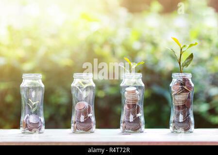 L'argent l'épargne et l'investissement concept: pièces empilées dans l'étape 4 de plus en plus avec des plantes sur table en bois avec fond nature. Montre investissement durable Banque D'Images