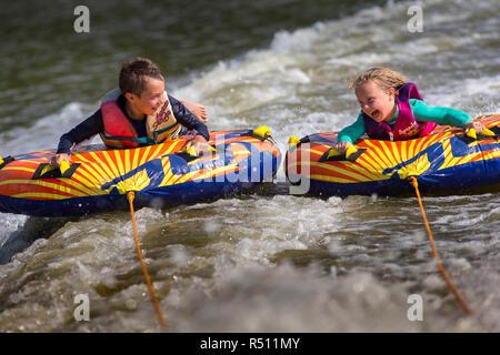 Vue de face de deux enfants s'amusant sur river Banque D'Images