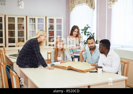 Dépenses diverses multiracial students temps libre dans la bibliothèque avec de grands vieux livre Banque D'Images