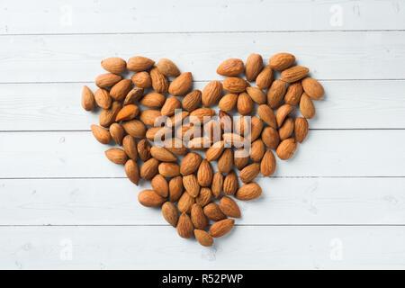 Les amandes sont desserrés en forme de cœur sur la table. Selective focus Banque D'Images