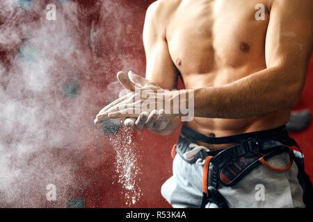 Revêtement de l'homme ses mains dans la craie en poudre Préparation magnésium à grimper, motion Banque D'Images