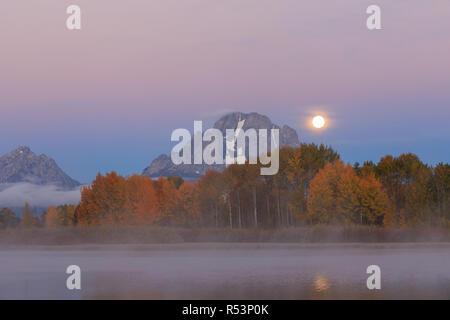 Pleine lune se couche sur le Tetons en automne