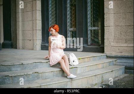 Boit du café dans une tasse. femme aux cheveux teints en rouge dans une robe rose pâle de boire du café, tenant une tasse de café en papier pour aller, assis sur les marches à l'extérieur d'une journée d'été. Banque D'Images
