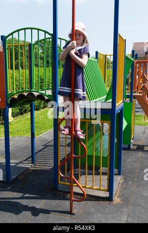 Fillette de six ans joue sur escalade bars en swing park à Havenstreet, Haven Street Route principale, à l'île de Wight, Royaume-Uni Banque D'Images