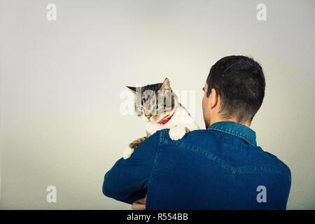 Vue arrière du jeune homme portant veste bleu jeans serrant un mignon et curieux cat holding à épaule. L'amour et du soin des animaux plus isolés grey wall background