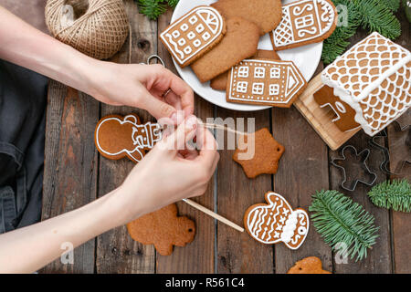 Une jeune fille décore ginger cookies sous la forme d'hiver Noël Bonhomme de matin. Cerise sur le miel attire femme gingerbread cookies. Table marron en bois. copier l'espace. Banque D'Images