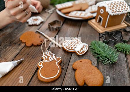 Une jeune fille décore ginger cookies sous la forme d'étoiles d'hiver noël matin. Cerise sur le miel attire femme gingerbread cookies. Table marron en bois. copier l'espace. Banque D'Images