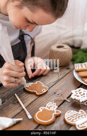 Les cookies dans la forme de moufles. Une jeune fille décore ginger cookies hiver matin de Noël. Femme attire cerise sur le miel d'épices . Table marron en bois. copier l'espace. Banque D'Images