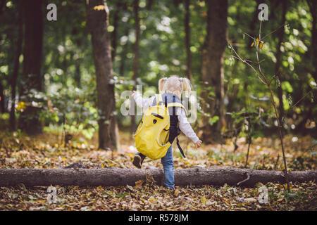 Le thème les enfants Activités de plein air. Drôle de petit bébé caucasien fille blonde promenades à travers forêt surmonter les obstacles, arbre est tombé, log. Grand sac à dos de randonnée bébé drôle en automne forest park Banque D'Images