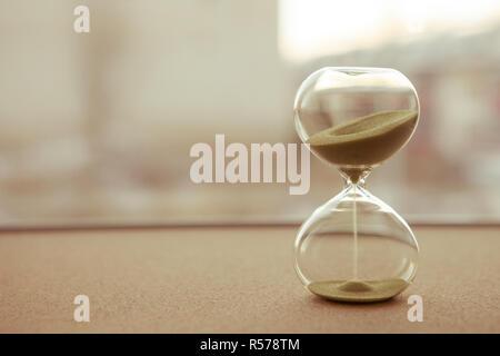 Le sable dans les vases du sablier mesurant le temps qui passe dans un compte à rebours jusqu'à une date limite, sur un arrière-plan flou Banque D'Images