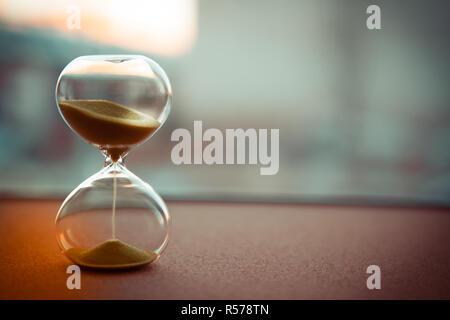 Le sable dans les vases du sablier mesurant le temps qui passe dans un compte à rebours jusqu'à une date limite, sur un arrière-plan flou with copy space Banque D'Images