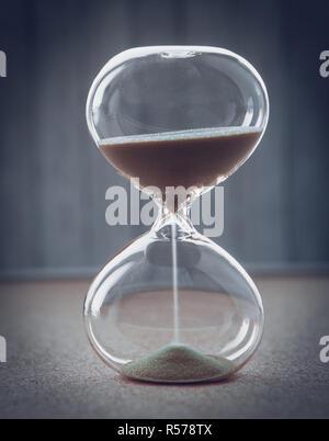 La mesure d'Hourglass passant du temps dans un compte à rebours jusqu'à une date limite, sur un arrière-plan flou with copy space Banque D'Images