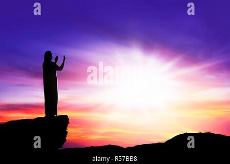 Silhouette of man à prier Dieu avec rayon de lumière Banque D'Images