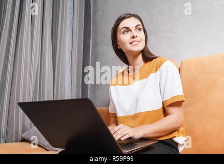 Jolie fille brune assise sur le canapé jaune à la lumière salle de séjour tout en travaillant avec son ordinateur portable et à la technologie moderne, plus loin, communication concept