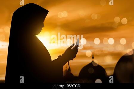 Silhouette de femme musulmane en prière avec le chapelet