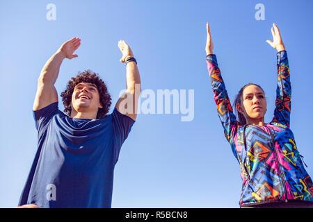 Couple stretching remise en forme en plein air dans le parc. Jeune homme et femme exerçant ensemble en matinée.
