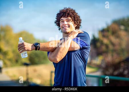 Smiling man stretching outdoors - Fitness, sport, la formation et le mode de vie concept