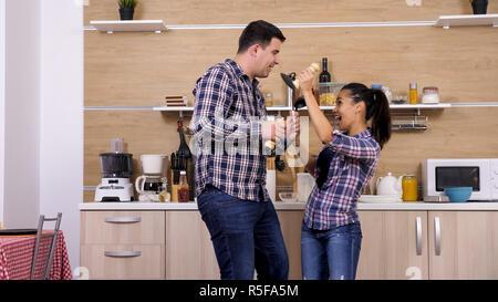Jeune couple couchait dans la cuisine tout en préparant le dîner. Drôle de couple. Banque D'Images