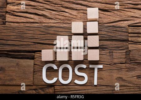 Texte en augmentant le coût des blocs de graphique à barres sur bois Banque D'Images