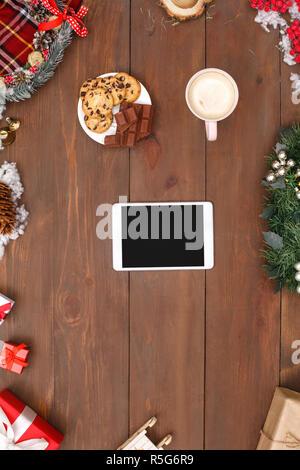 Joyeux Noël. Tablette numérique de la plaque de cookies et chocolat tasse de cacao isolé sur table décoration top view close-up Banque D'Images