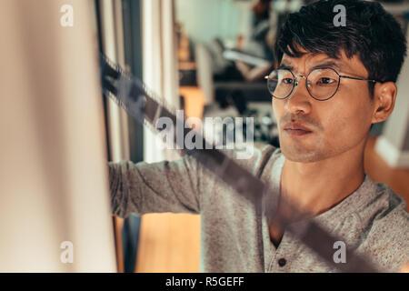 Contrôle photographe 35mm inclu en face de la fenêtre. L'homme choisit une trame sur de vieux film. Banque D'Images