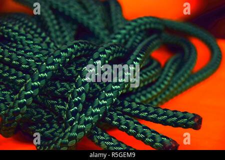 La corde de nylon vert avec l'accent sur les extrémités en face de fond orange, nouvelle corde verte pour la macro shot voyage ou la santé ou l'industrie du sport Banque D'Images