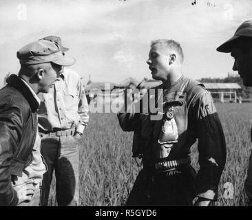 Ensign Neil A. Armstrong, US Navy, (futur astronaute de la NASA et le premier homme à marcher sur la lune lors de la mission Apollo 11) raconte le colonel Carlson A. Roberts, USMC, et deux autres hommes non identifiés de la peine qui lui a permis de sortir de son F9F 'Panther' jet au-dessus de la Corée, le 18 septembre 1951. Banque D'Images