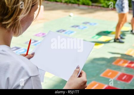 Une jeune fille tenant une feuille d'été blanc Banque D'Images