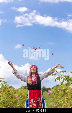 Fille bulgare habillés en vêtements traditionnels pierres rose dans l'air pendant le festival annuel a augmenté dans la région de Kazanlak, Bulgarie Banque D'Images