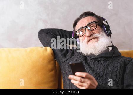 Joyeux Senior homme barbu portant des lunettes en pull gris avec le smartphone de détente tout en restant assis dans le casque sur un canapé jaune dans sa lumière, salon de la technologie moderne, communication concept Banque D'Images