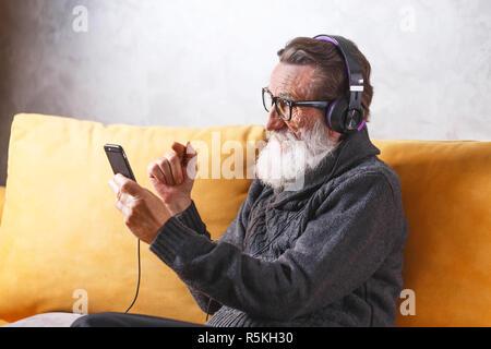 Joyeux Senior homme barbu portant des lunettes en pull gris smartphone à l'aide tout en restant assis dans le casque sur un canapé jaune dans sa lumière, salon de la technologie moderne, communication concept