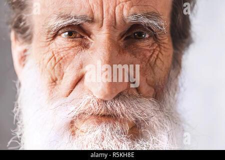 Portrait of senior man barbu gaie contemporaine avec les rides en chemise blanche debout sur le fond gris, la technologie moderne, communication concept Banque D'Images