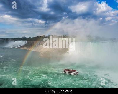 Le bateau entouré de brume sous les chutes du Niagara en passant sous l'arc en ciel. Banque D'Images