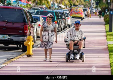 Floride Miami Beach Ocean Drive trottoir senior homme femme couple voitures en stationnement à pied physiquement handicapés en fauteuil roulant électrique im Banque D'Images
