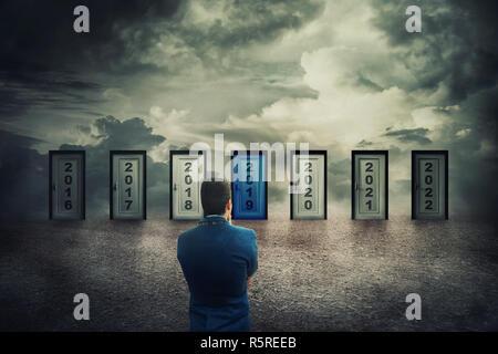 Vue arrière homme devant de nombreuses portes avec différents numéros d'années. Décision difficile, la notion de choix important dans la vie, choisissez de vivre le pré Banque D'Images