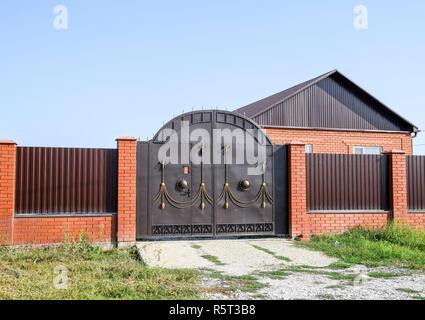 Maison de brique avec une clôture et des barrières. Vue d'une nouvelle agglomération clôture et une maison faite de briques et de métal ondulé. Banque D'Images
