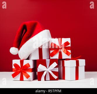 Noël rouge et blanc boîtes cadeaux en forme de pyramide avec Santa hat sur le dessus sur fond rouge Banque D'Images