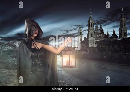 Jeune sorcière avec cape noire holding lantern Banque D'Images